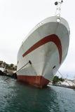 Le bateau blanc avec une rayure rouge est dans un port Image libre de droits