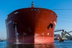 Le bateau décharge le granit dans le port Images libres de droits