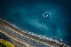 Le bateau dans l'océan va sur la spirale n'est pas loin de la côte Images libres de droits