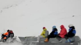 Le bateau de banane de neige avec des touristes glisse vers le bas la pente accidentée banque de vidéos