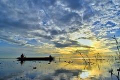 Le bateau de dérive sur le backgrund de lever de soleil de mer Images stock