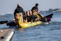 Le bateau de dragon entre dans la jetée après une course Images stock