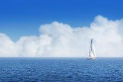 Le bateau de navigation fait de la navigation de plaisance avec les voiles blanches et le ciel nuageux image stock