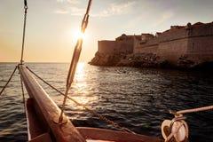Le bateau de navigation navigue dans le coucher du soleil près de Dubrovnik Photographie stock libre de droits