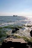 Le bateau de pêche en mer près de l'horizon, ressac heurte les roches Photographie stock