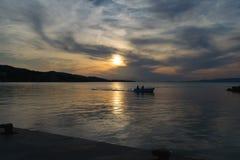 Le bateau de pêche silhouettent le renvoi au port contre un ciel dramatique images stock
