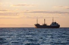 Le bateau de pêche va pêcher en soirée au coucher du soleil photo libre de droits