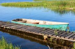 Le bateau de pêche a amarré à un pilier sur le lac pendant le matin Image libre de droits