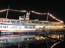 Le bateau de restaurant illumine les rivages de la luzerne de lac à la tombée de la nuit photographie stock libre de droits