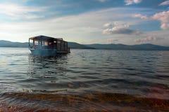 Le bateau de touristes flotte sur l'eau Photographie stock