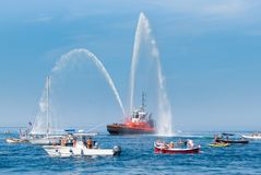Le bateau des sapeurs-pompiers avec la haute éclabousse au ciel images stock