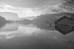Le bateau dramatique de paysage et le hangar à bateaux en bois sur le lac pur ont saigné à la lumière du soleil directe en hiver Images libres de droits