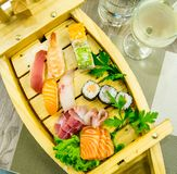 Le bateau en bois exquis a rempli avec différents types de morceaux de sushi et de poissons Photos libres de droits