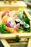 Le bateau en bois exquis a rempli avec différents types de morceaux de sushi et de poissons Photo libre de droits