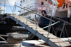 Le bateau est amarré à une chaîne de corde d'échelle de dock image libre de droits