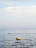 Le bateau et les canoës s'approchent du bord de mer dans Giardini Naxos Image stock