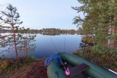 Le bateau gonflable avec deux tournant sur le lac au lever de soleil Images stock