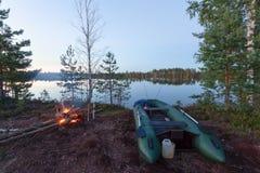 Le bateau gonflable avec deux tournant sur le lac au lever de soleil et au feu Photos libres de droits