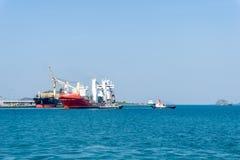 Le bateau gros porteur de grandes cargaisons laisse le port avec soutenu en deux remorqueurs photos libres de droits
