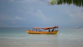 Le bateau jaune de longtail part avec des touristes de la belle plage blanche banque de vidéos