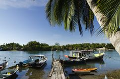 Le bateau malaisien traditionnel de pêcheur a amarré, jetée en bois et fond de ciel bleu photographie stock