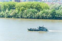 Le bateau militaire ou le petit bateau avec le camouflage colore la navigation en bas de la rivière Photos libres de droits