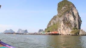 le bateau ornementé de longtail navigue jusqu'au village de logements de pile banque de vidéos