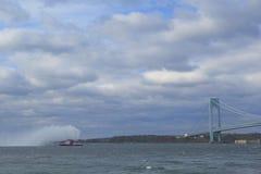 Le bateau-pompe de FDNY pulvérise l'eau dans l'air pour célébrer le début du marathon 2014 de New York City dans l'avant du pont  Image stock
