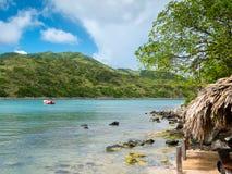 Le bateau rouge attend outre de la plage tropicale Photo stock
