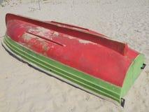Le bateau rouge et vert a tourné vers le haut du côté vers le bas jusqu'au sable images stock