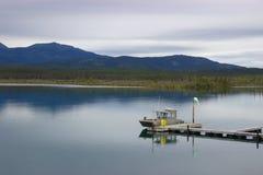 Le bateau s'est accouplé dans le lac tranquille de montagne, le Yukon, Canada Images stock