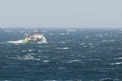 Le bateau semble couler dans les grandes vagues de la tempête d'océan arctique Images libres de droits