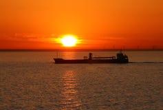 Le bateau sur un coucher du soleil. Images stock