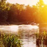 Le bateau tire le ski d'eau d'homme sur la rivière Coucher du soleil Éclabousse de l'eau images stock
