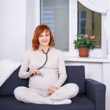 Le battement de coeur du bébé de écoute de femme enceinte avec le stéthoscope à ho Photo stock