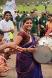 Le batteur de sourire heureux de femme joue le tambour dans un rassemblement image stock