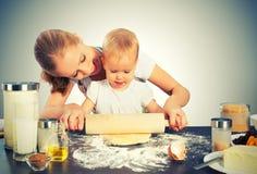 Le bébé avec sa cuisinière de mère, font cuire au four Photographie stock