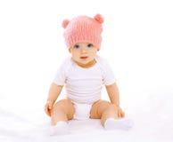 Le bébé doux s'asseyant dans le rose a tricoté le chapeau Photos libres de droits