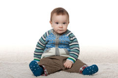 Le bébé garçon de mode s'asseyent sur le tapis blanc Photo libre de droits