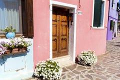 Le beau bâtiment avec le pétunia fleurit en île de Burano (Venise, Italie) Photo libre de droits