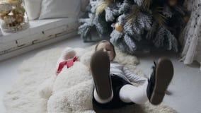 Le beau bébé joue joyeux avec un grand nounours blanc concernent le plancher près de l'arbre de Noël dans le salon banque de vidéos