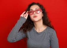 Le beau baiser de vol de portrait de jeune femme, posant sur le fond rouge, les longs cheveux bouclés, lunettes de soleil au coeu Photos stock