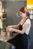 Le beau barman féminin de l'Asie fait le café glacé sur le café Images stock