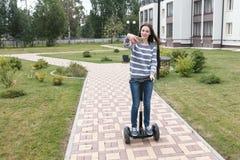 Le beau blogger de femme de brune raconte une histoire aux abonnés sur le roulement de téléphone portable sur le scooter de compa photographie stock