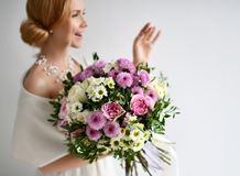 Le beau bouquet de prise de femme du chrysanthème et des roses fleurit le sourire heureux blanc et pourpre sur le gris photo stock