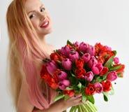 Le beau bouquet de prise de femme de la tulipe rouge et rose fleurit le sourire heureux sur le gris photographie stock