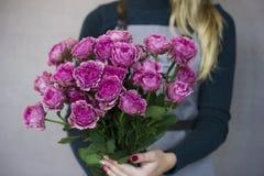 Le beau bouquet des roses roses dans des mains femelles sur le fond gris Photo stock