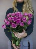 Le beau bouquet des roses roses dans des mains femelles sur le fond gris Photos stock