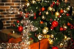 Le beau cerf commun de Noël avec rougeoyer s'allume la nuit dans le salon avec l'arbre de Noël décoré, cadeaux An neuf photos stock