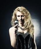Le beau chanteur blond de femme dans une robe noire tenant un microphone et chante une chanson Photos libres de droits